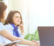 Mujer de negocios acertada con los colegas que hablan en el teléfono Foto de archivo libre de regalías