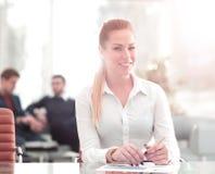 Mujer de negocios acertada con su personal en fondo en la oficina fotos de archivo