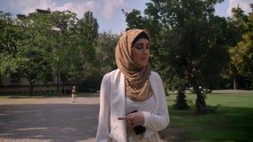 Mujer de negocios acertada confiada que camina en parque y que mira alrededor, día soleado afuera, sonrisa femenina hermosa almacen de metraje de vídeo