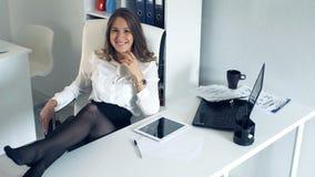 Mujer de negocios acertada en la oficina con sus pies en el escritorio almacen de metraje de vídeo