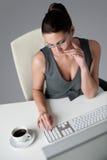Mujer de negocios acertada en la oficina que come café Foto de archivo