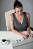 Mujer de negocios acertada en la oficina que come café Fotos de archivo