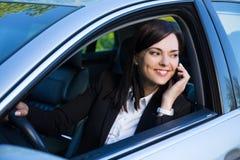 Mujer de negocios acertada feliz que habla en el teléfono en su coche Imagenes de archivo