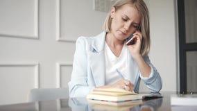 Mujer de negocios acertada hermosa y joven que habla con el teléfono y que hace notas en libreta en un café, haciendo almacen de video