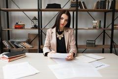 Mujer de negocios acertada que comprueba la documentación Foto de archivo libre de regalías