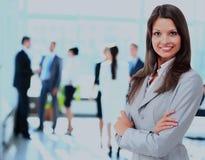 Mujer de negocios acertada que se coloca con su personal en fondo en la oficina Fotos de archivo