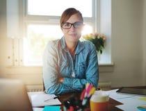 Mujer de negocios acertada que trabaja en la oficina imagen de archivo