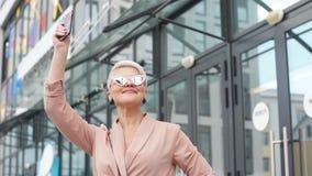 Mujer de negocios adulta con PC de la tableta con el distrito de oficina en fondo almacen de metraje de vídeo