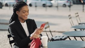 Mujer de negocios afro elegante usando el café de consumición del smartphone que se sienta en la terraza del verano en café acoge metrajes