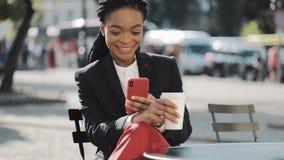 Mujer de negocios afro elegante usando el café de consumición del smartphone que se sienta en la terraza del verano en café acoge almacen de video