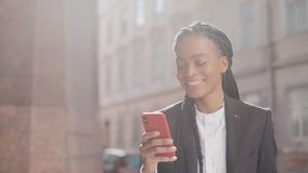 Mujer de negocios afro elegante usando smartphone que camina en la calle cerca de centro de negocio Elegante negro dreadlocks afr metrajes