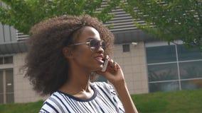 Mujer de negocios afroamericana atractiva joven en gafas de sol que habla en el teléfono móvil y la sonrisa metrajes