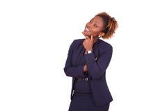 Mujer de negocios afroamericana con los brazos doblados que miran para arriba, i Imagen de archivo