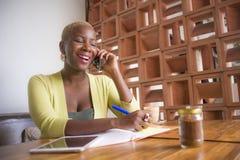 Mujer de negocios afroamericana negra elegante y hermosa joven que trabaja en línea con el teléfono móvil en la cafetería que tom foto de archivo