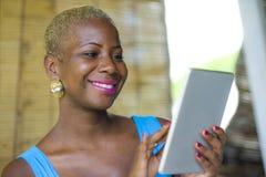 Mujer de negocios afroamericana negra elegante y elegante joven que trabaja en la cafetería de moda usando el cojín digital de la fotos de archivo libres de regalías