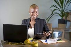 Mujer de negocios afroamericana negra feliz y acertada que trabaja en la sonrisa moderna de la oficina alegre usando el cojín dig fotografía de archivo libre de regalías