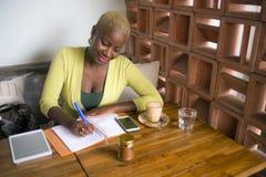 Mujer de negocios afroamericana negra hermosa joven que trabaja en las notas que toman felices sonrientes de la cafetería en libr imagen de archivo libre de regalías