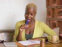 Mujer de negocios afroamericana negra hermosa joven que trabaja en las notas que toman felices sonrientes de la cafetería en libr Imagenes de archivo