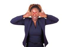 Mujer de negocios afroamericana que la oculta ojos con su mano Foto de archivo