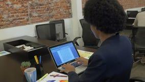 Mujer de negocios afroamericana que mecanografía usando empresarios del ordenador portátil