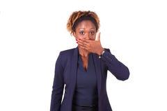 Mujer de negocios afroamericana que oculta su boca con su mano Imagenes de archivo