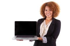 Mujer de negocios afroamericana que sostiene un ordenador portátil - personas negras Foto de archivo