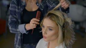 Mujer de negocios agradable con maquillaje en un salón de belleza El peluquero profesional hace el peinado para los blondes almacen de video