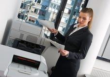 Mujer de negocios al lado de la impresora de oficina Imágenes de archivo libres de regalías