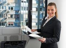 Mujer de negocios al lado de la impresora de oficina Fotos de archivo