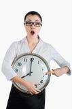 Mujer de negocios alarmada, chocada que sostiene un reloj grande ISO blanca imagen de archivo