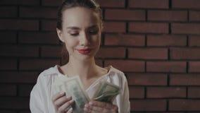 Mujer de negocios alegre que cuenta el dinero para las inversiones rentables en estudio del ladrillo almacen de metraje de vídeo