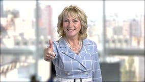 Mujer de negocios alegre que gesticula los pulgares para arriba metrajes