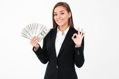 Mujer de negocios alegre que muestra el gesto aceptable que sostiene el dinero Fotografía de archivo