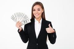 Mujer de negocios alegre que muestra los pulgares que detienen el dinero Foto de archivo libre de regalías