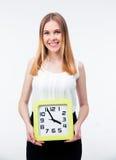 Mujer de negocios alegre que se coloca que sostiene el reloj grande Fotos de archivo