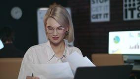Mujer de negocios alegre que trabaja en el ordenador portátil en oficina Muchacha del primer que comprueba el papel metrajes