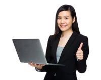Mujer de negocios asiática con el ordenador portátil y el pulgar para arriba Foto de archivo