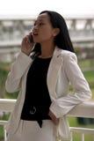 Mujer de negocios asiática con el teléfono celular que mira apagado Fotos de archivo libres de regalías