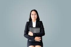 Mujer de negocios asiática con el traje de trabajo que se sienta con el fichero del docu Foto de archivo