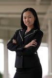 Mujer de negocios asiática con la sonrisa plegable brazos Imagen de archivo libre de regalías
