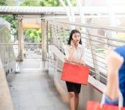 Mujer de negocios asiática confiada joven que habla en el teléfono móvil con los bolsos que hacen compras coloridos que camina imagen de archivo libre de regalías