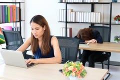 Mujer de negocios asiática envidiosa que trabaja con el colega del competidor que duerme en oficina imagenes de archivo