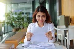 Mujer de negocios asiática feliz atractiva que sonríe con el papel del documento en su fondo de la oficina Fotografía de archivo