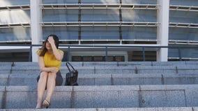 Mujer de negocios asiática frustrada que se sienta en las escaleras almacen de metraje de vídeo