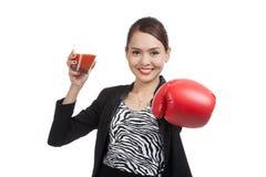 Mujer de negocios asiática joven con el jugo de tomate y el guante de boxeo Fotografía de archivo libre de regalías