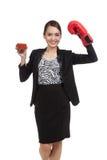 Mujer de negocios asiática joven con el jugo de tomate y el guante de boxeo Foto de archivo
