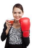 Mujer de negocios asiática joven con el jugo de tomate y el guante de boxeo Imágenes de archivo libres de regalías