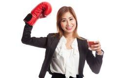 Mujer de negocios asiática joven con el jugo de tomate y el guante de boxeo Imagen de archivo