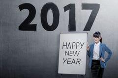 Mujer de negocios asiática joven con el ` s de la Feliz Año Nuevo que saluda sobre 2 Fotografía de archivo