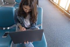 Mujer de negocios asiática joven del retrato que trabaja en el ordenador portátil en aeropuerto imágenes de archivo libres de regalías